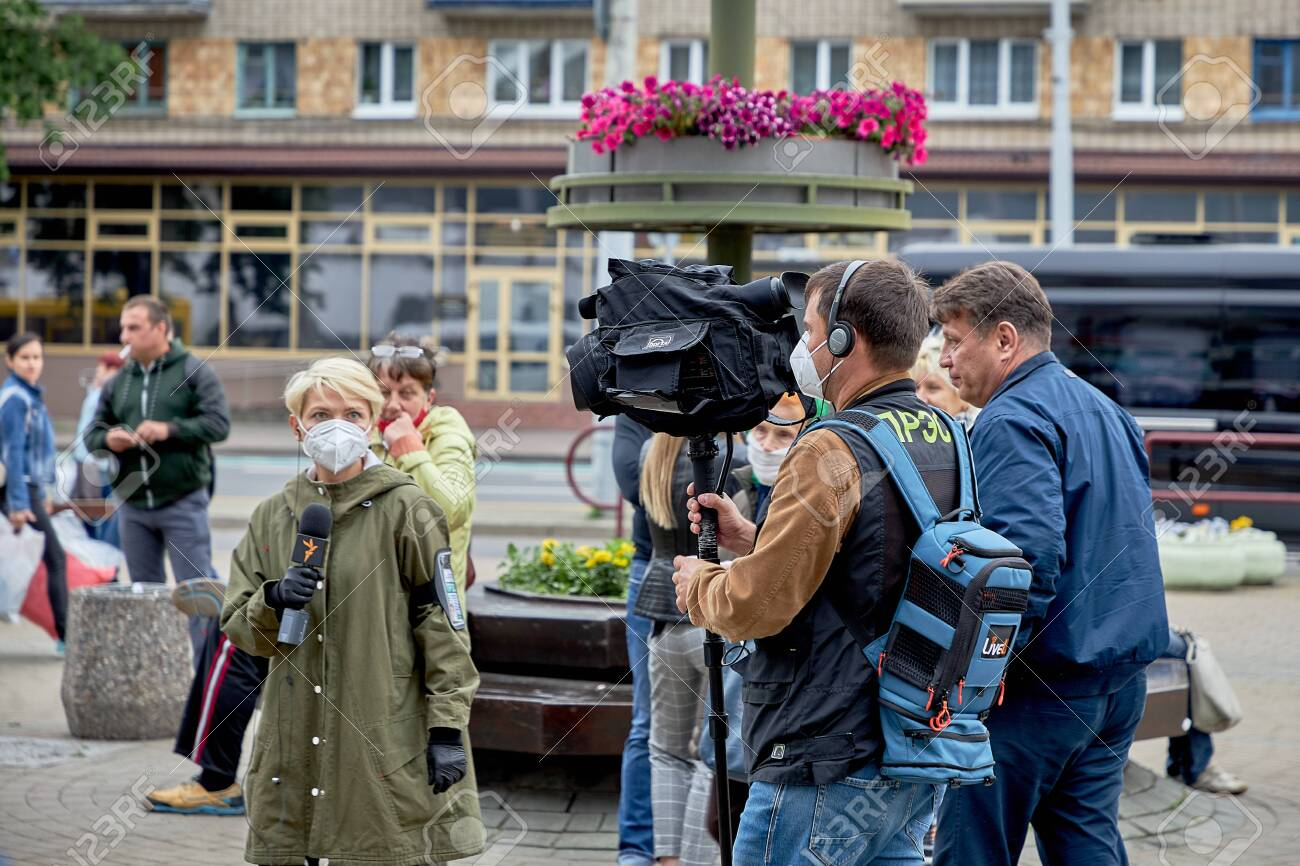 June 14 2020 Minsk Belarus A man with a large camera takes video of a female reporter with a microphone on the street - 151307344