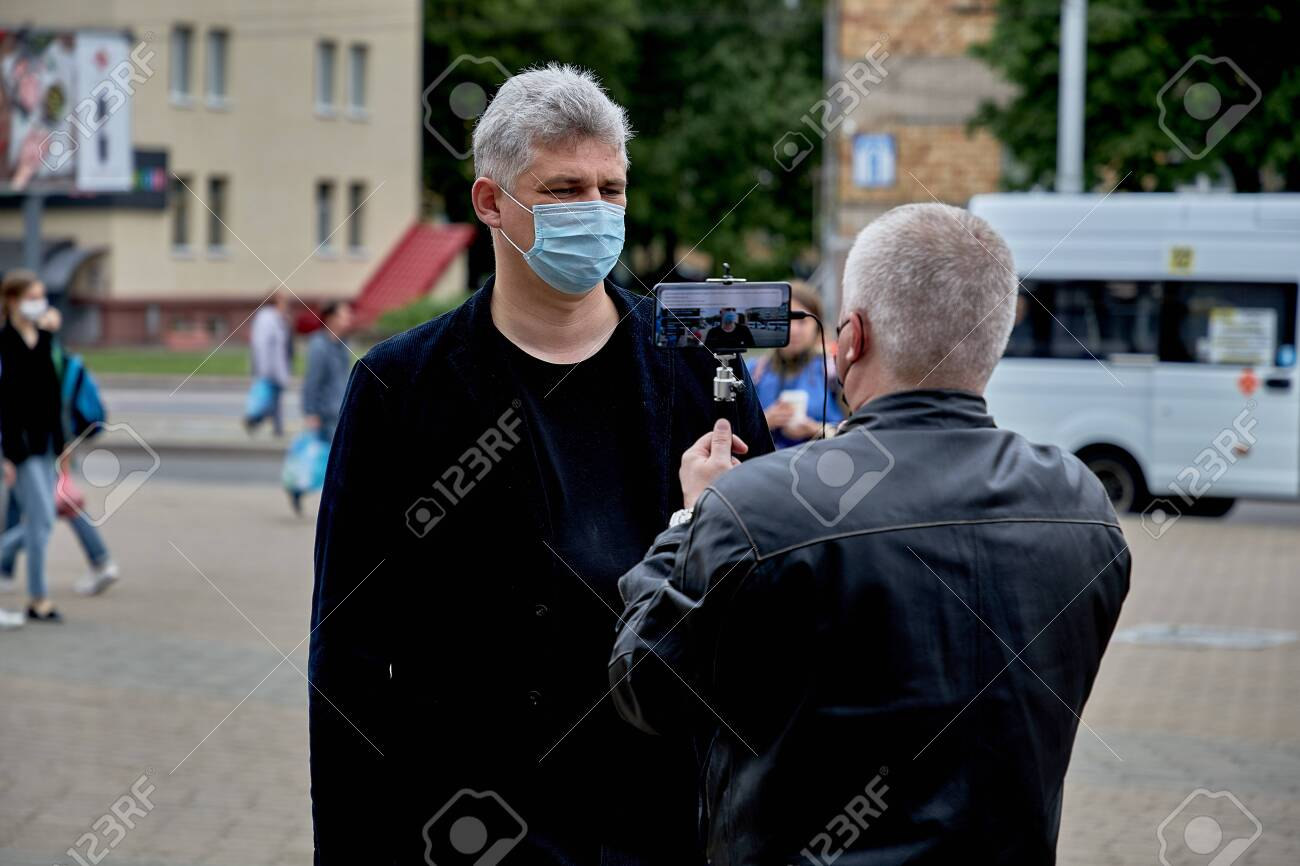 June 14 2020 Minsk Belarus There is a portrait of a masked man answering questions from a blogger who is filming it on his phone - 151307346