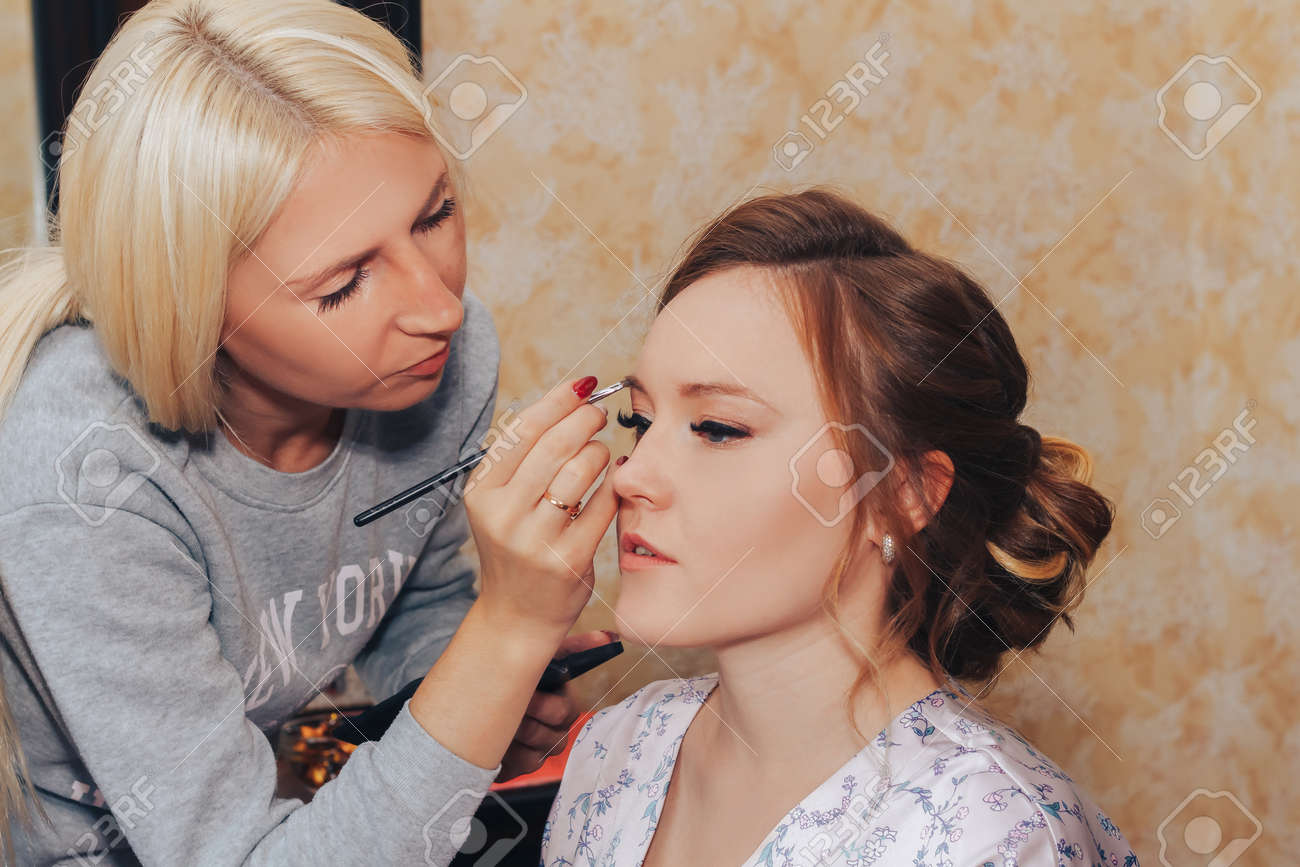 August 10, 2019 Minsk Belarus Makeup artist doing hairstyle to girl - 156649702