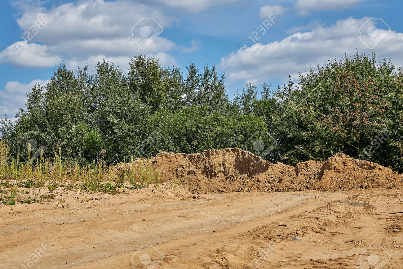 Sand lying for construction purposes against the blue sky - 160082166