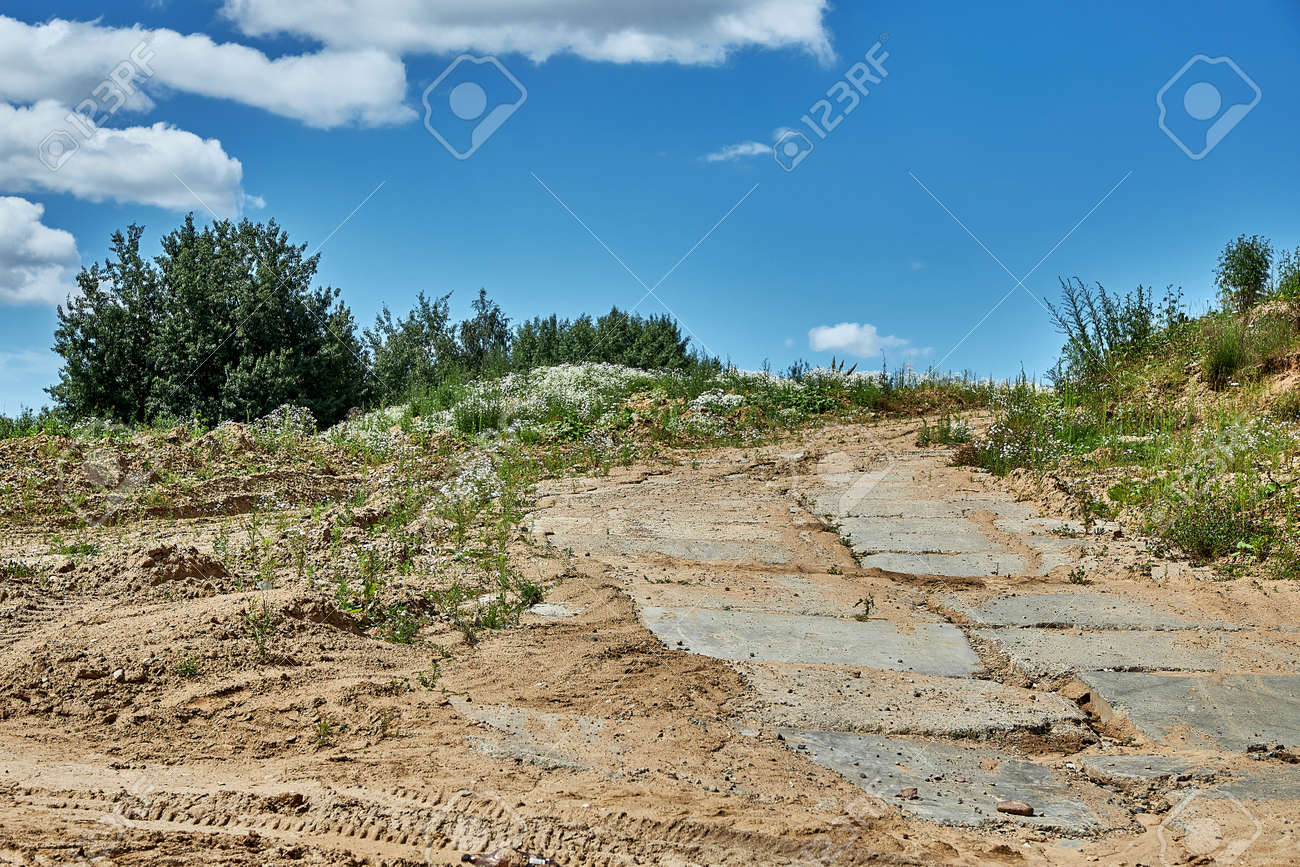 A road covered with concrete slabs leading to the construction site - 163142908