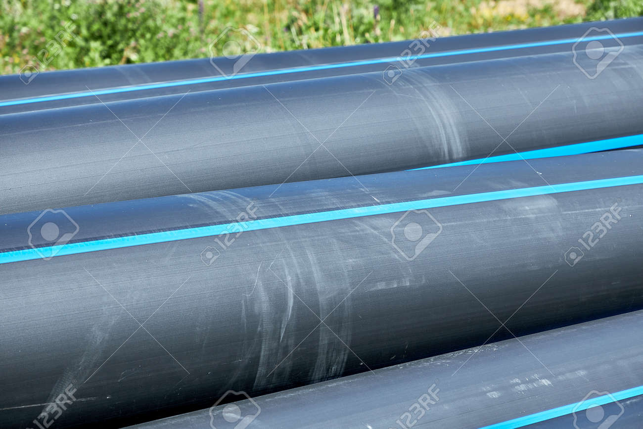 A lot of polyethylene pressure pipes lying outdoors during installation - 163142919