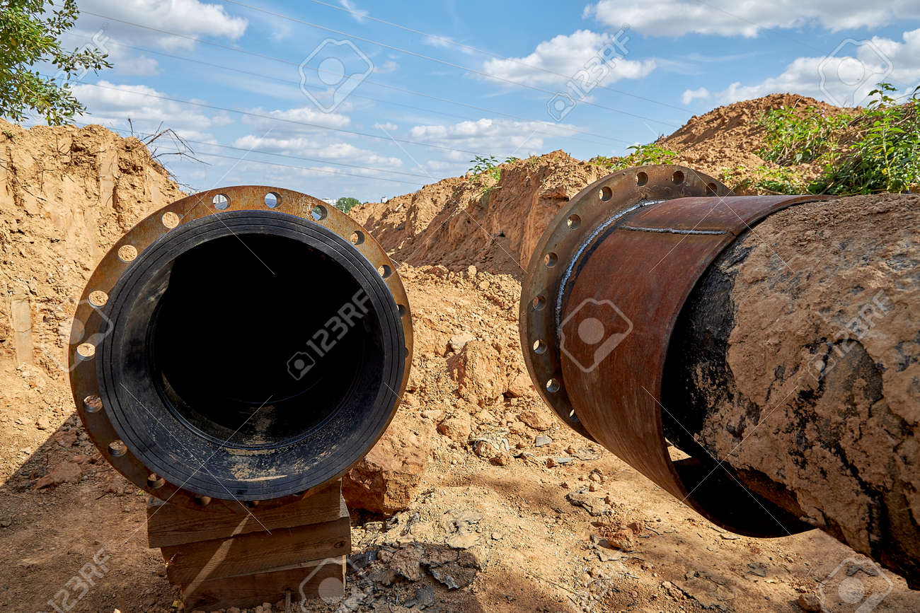 An old steel water pipe with a welded flange lies next to a new plastic pipe installed to connect the water - 170752374