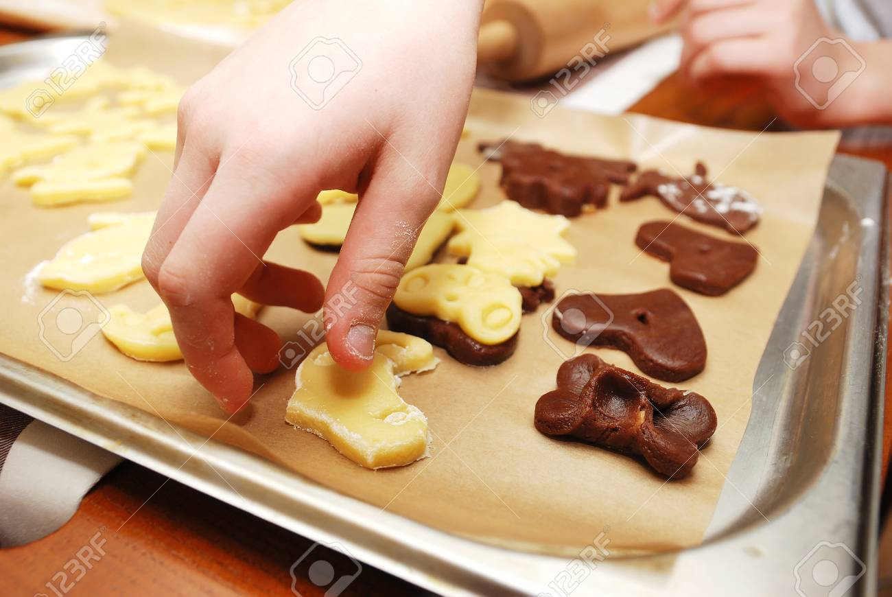 childrens hands making christmas cookies with metal cutter close up stock photo - Making Christmas Cookies