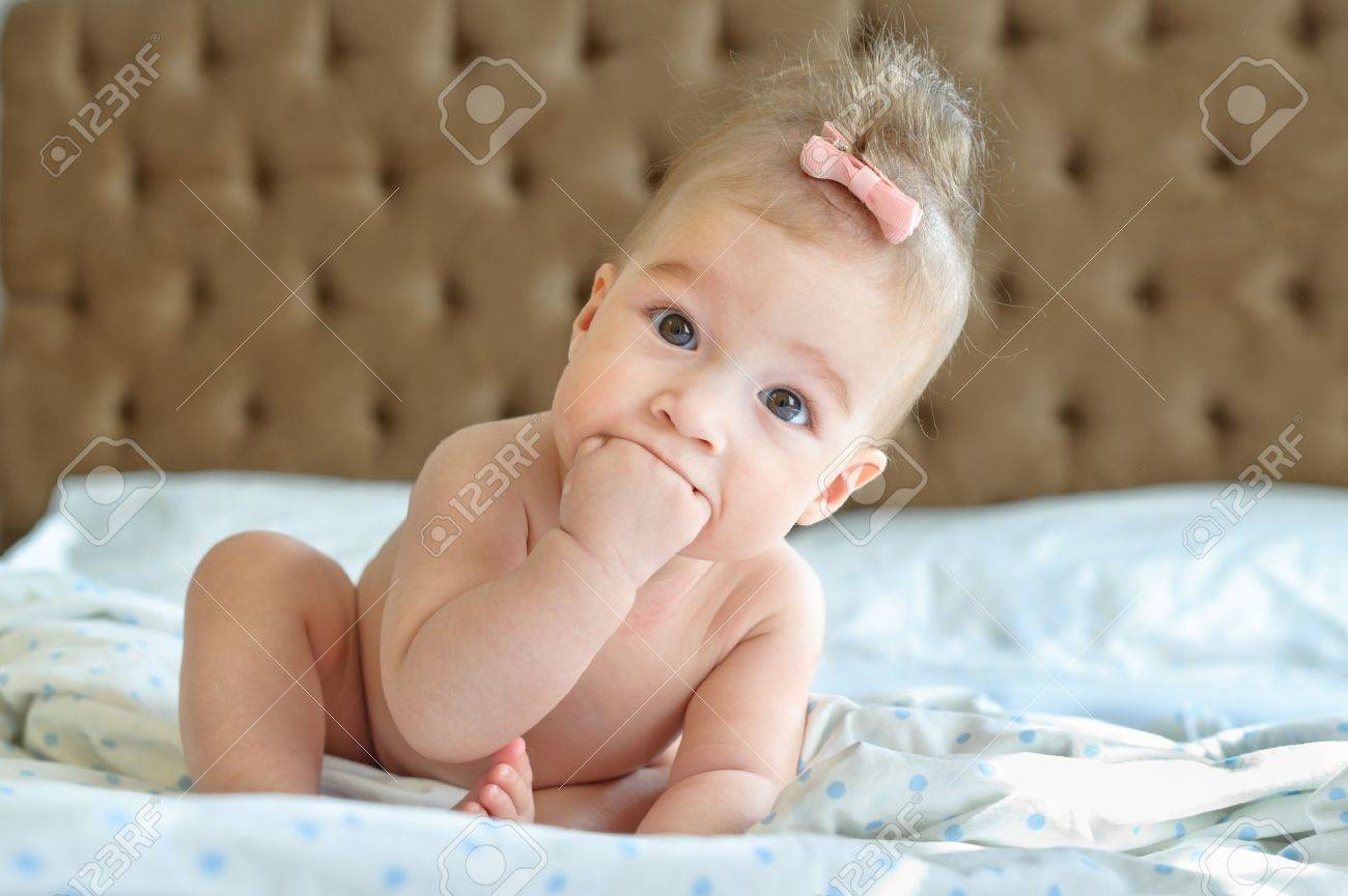 six months baby sitting on the bed fingers in her mouth Stock Photo - 15476175