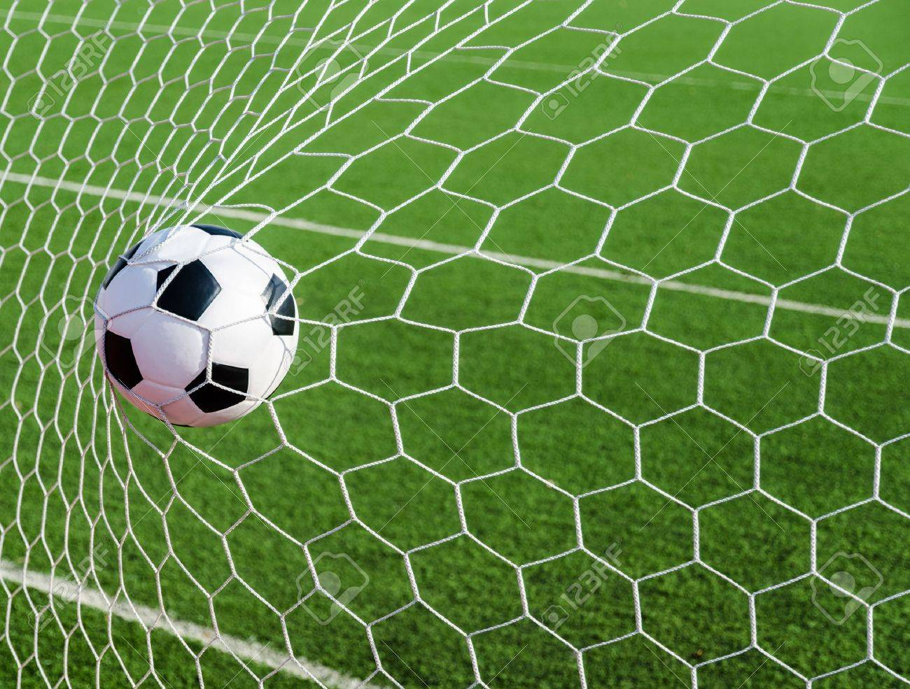 Soccer football in Goal net with green grass field Stock Photo - 18002764