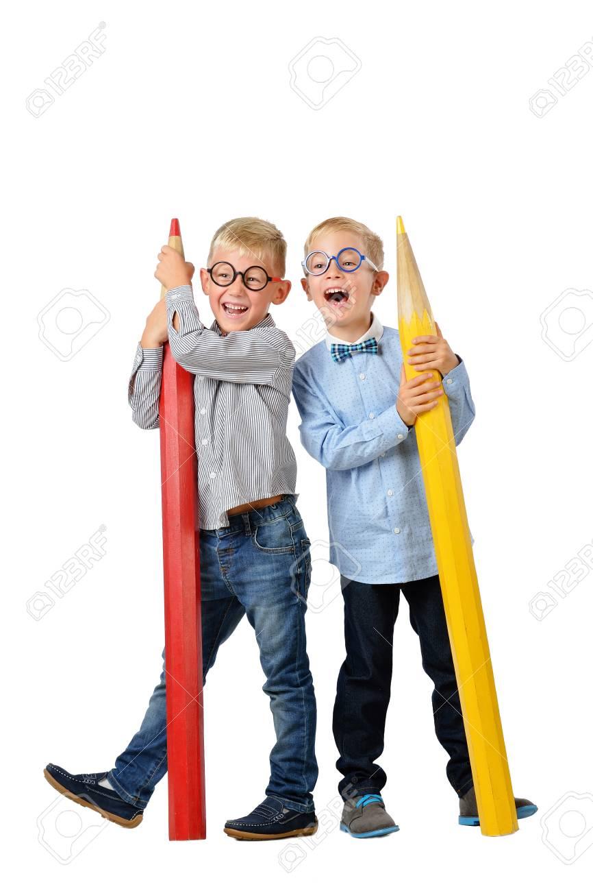 0bf3b3671b7 School preschool. Full length portrait happy young boys in glasses and  bowtie posing near huge colorful pencils.