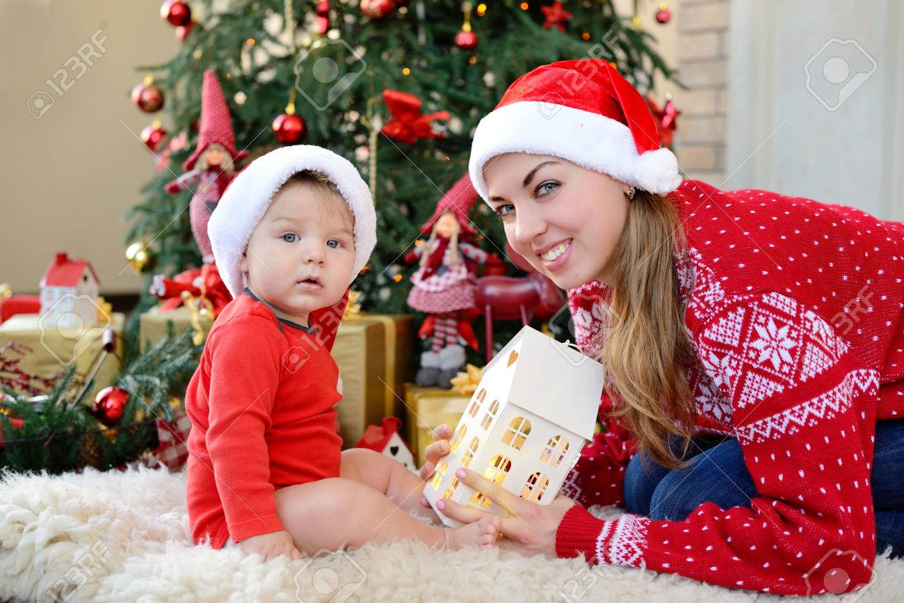 Pequeno Bebe Y La Madre Adorable En Los Sombreros De Santa Juego