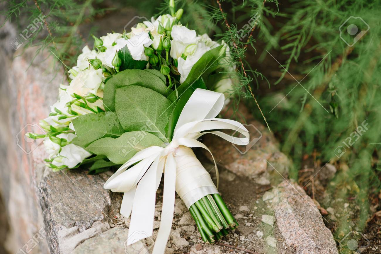 Close Up Of Wedding Bouquet With White Roses On Stone And Green