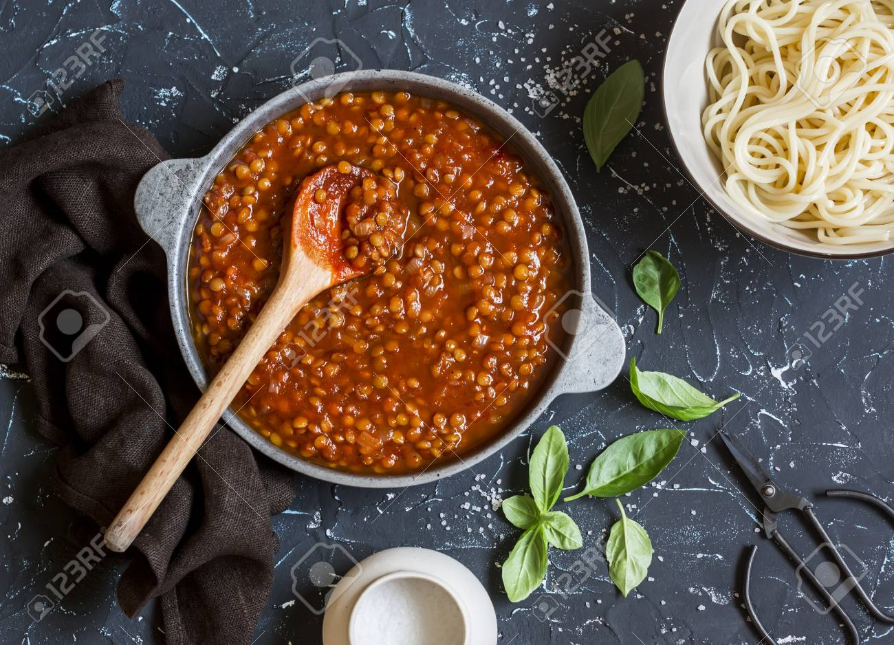 Vegetarian lentil bolognese sauce in a frying pan on a dark background. - 59762775