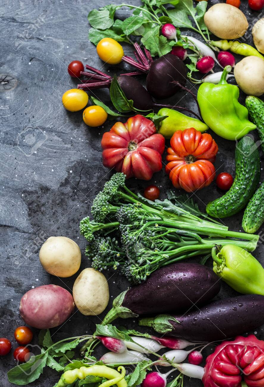 Fresh seasonal vegetables food background. Aubergines, tomatoes, radishes, peppers, broccoli, potatoes, beets on a dark background, top view. Flat lay - 129736469