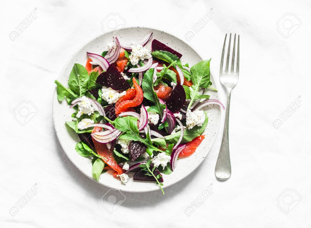 Beetroot, smoked salmon, arugula, soft cheese salad on a light background, top view - 135856122
