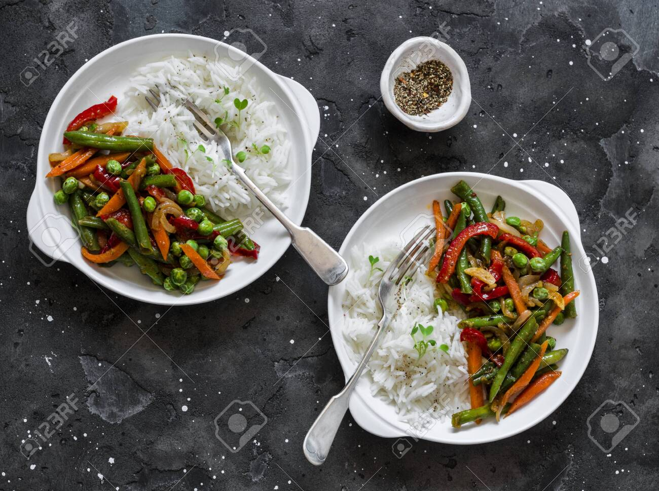 Green beans, sweet peppers, carrots, onions, green peas stir fry and rice on a dark background, top view. Fast diet vegetarian lunch - 144772798