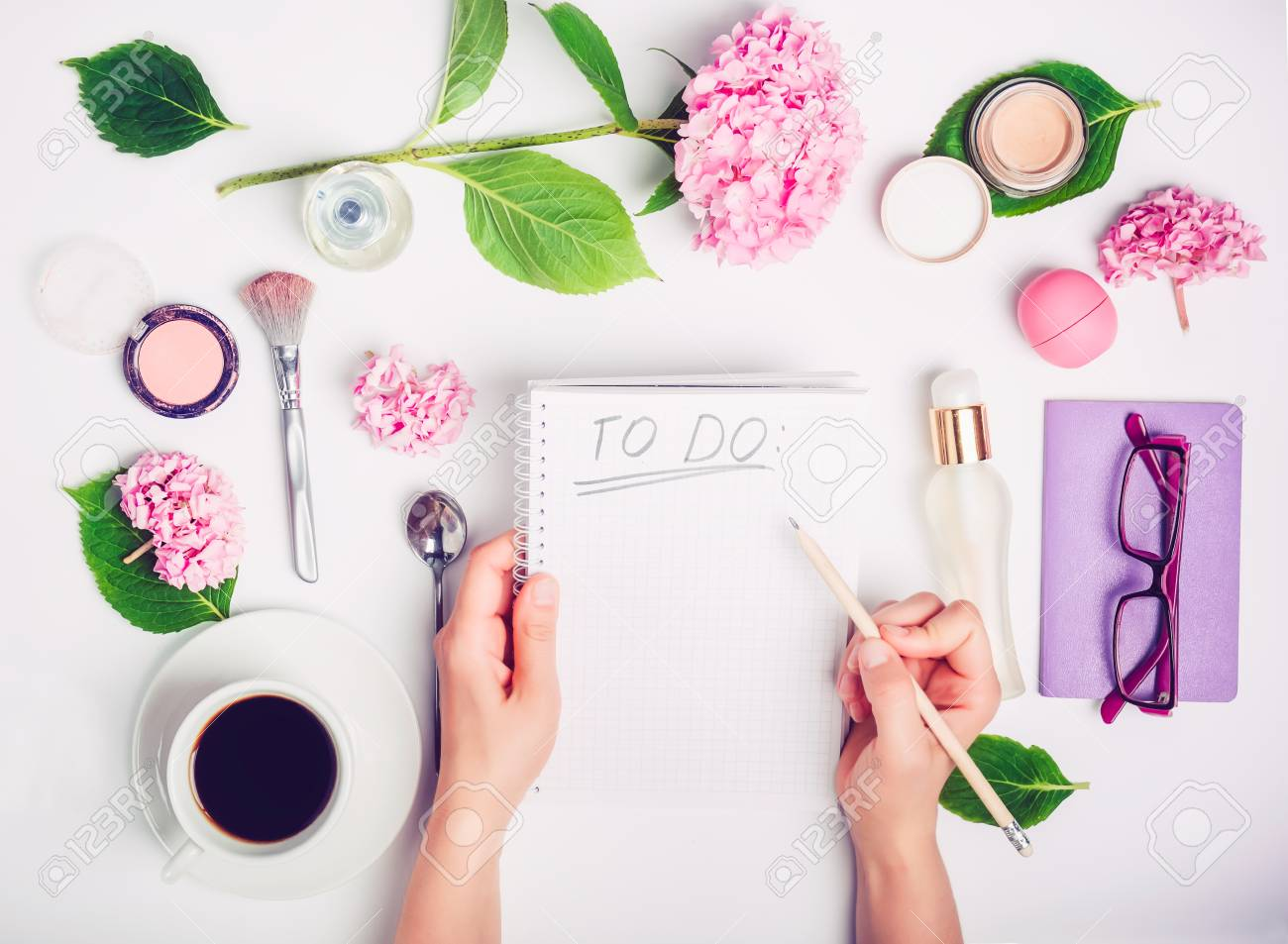 Female hands write To do list on the white working place with