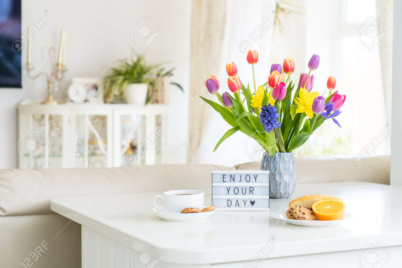 Good morning concept. Romantic breakfast - fresh spring flowers, cup of hot coffee drink, cookies, orange, lightbox with message Enjoy your day on marble table with light interior view. Copy space. - 166250059