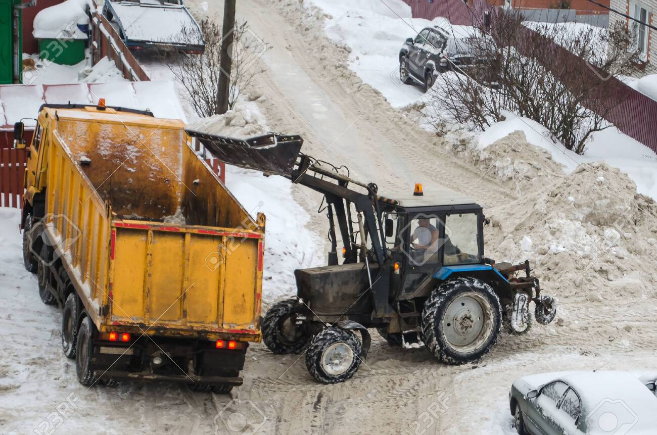 Snow cleaning tractor snow-removal machine loading pile of snow