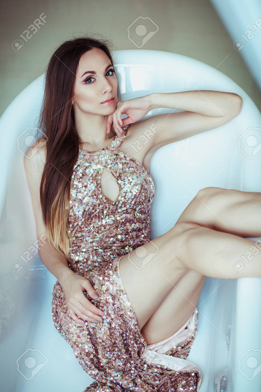 8ad4f7087b Beautiful stunning young woman in amazing glitter sequins dress lies in a  white bath. Bright