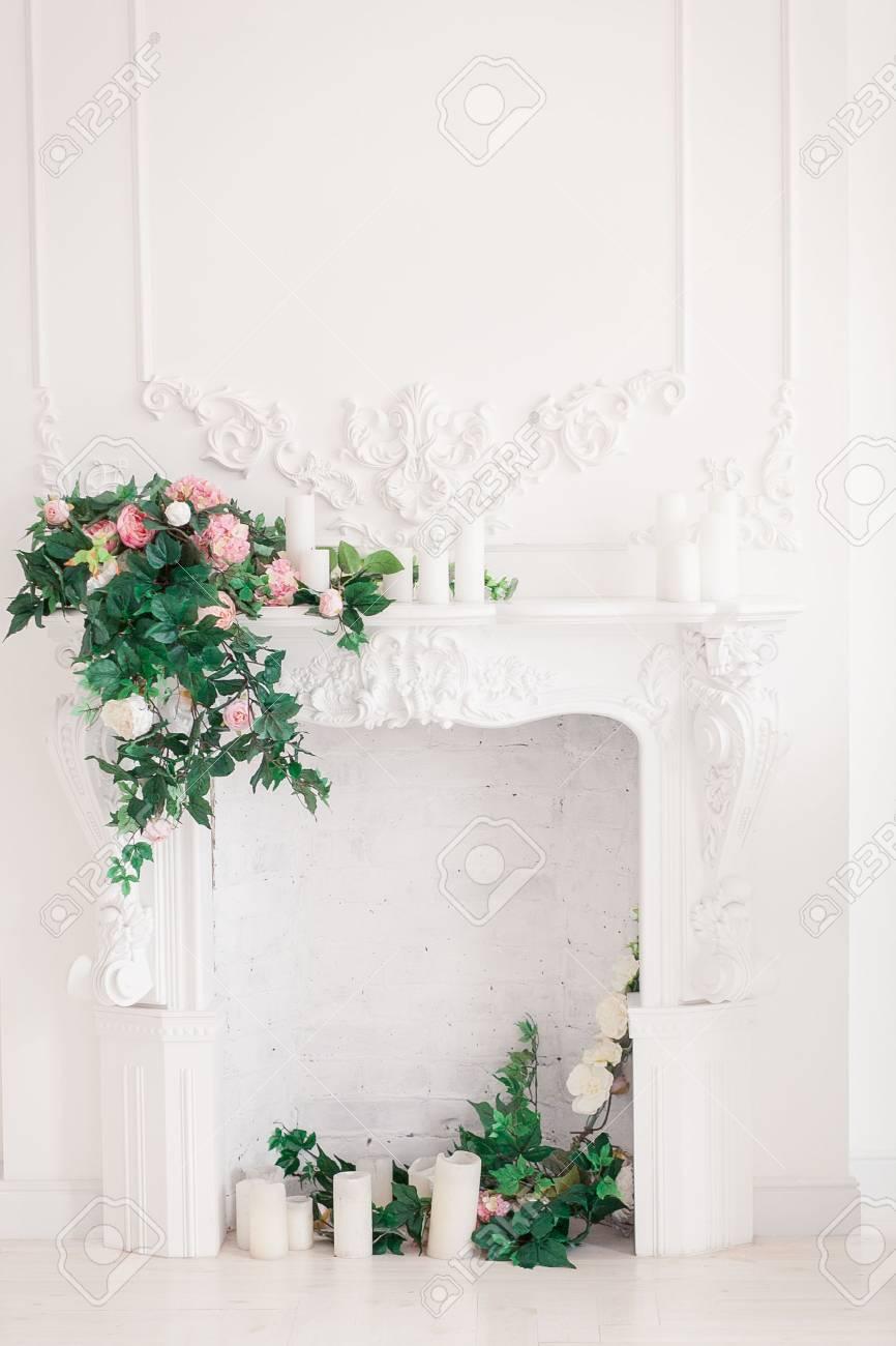 Interno classico bianco del soggiorno con camino e bouquet di fiori  primaverili su di esso