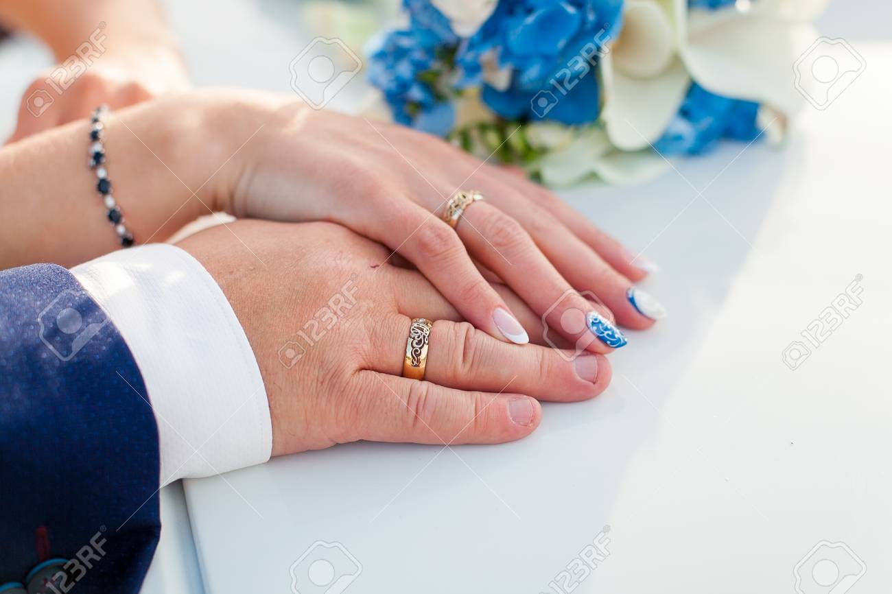 Bride And Groom Holding Hands With Wedding Rings On It Stock Photo ...