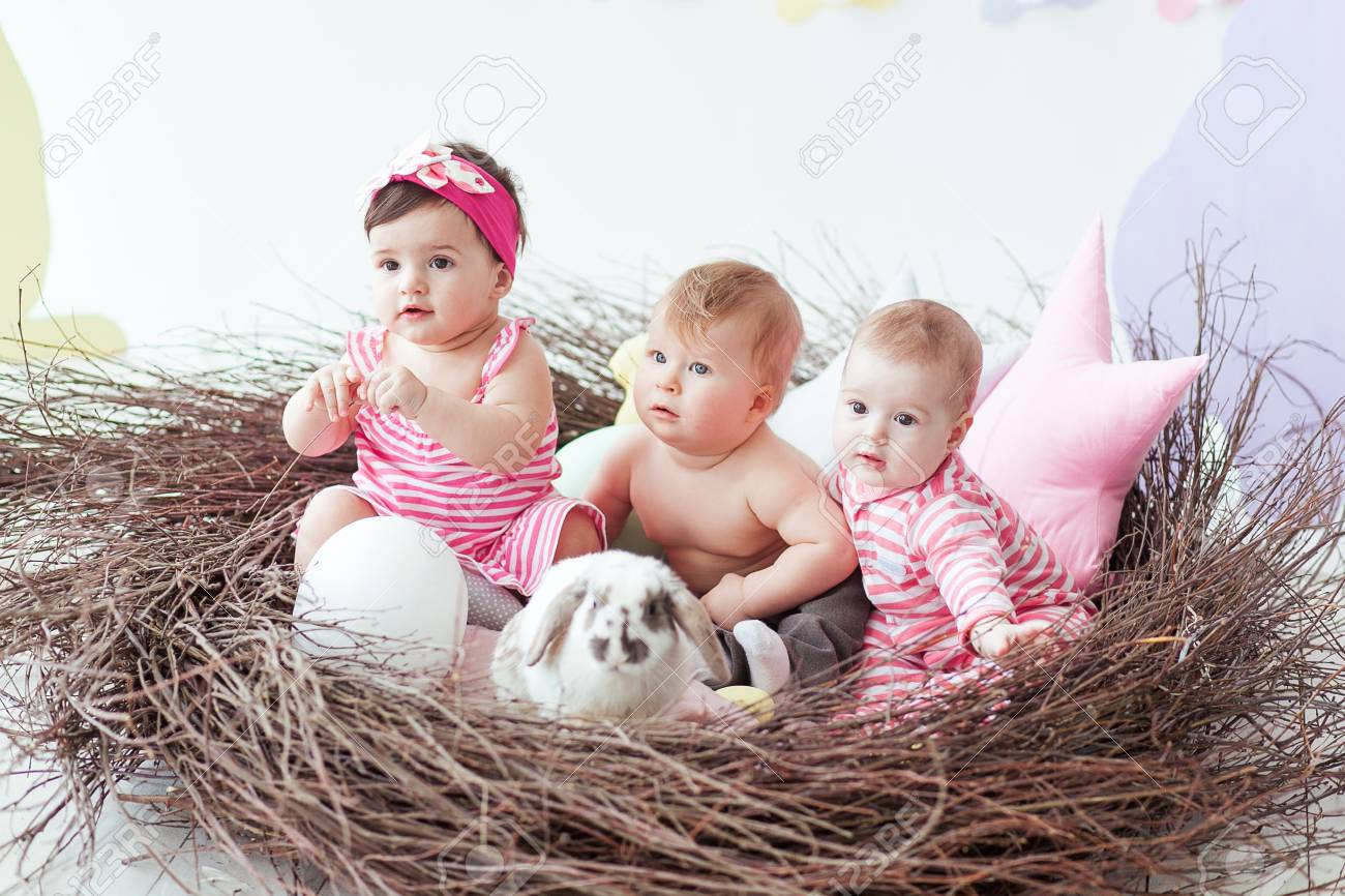 Three Cute Little Babies And Rabbit With Easter Eggs Sitting Stock