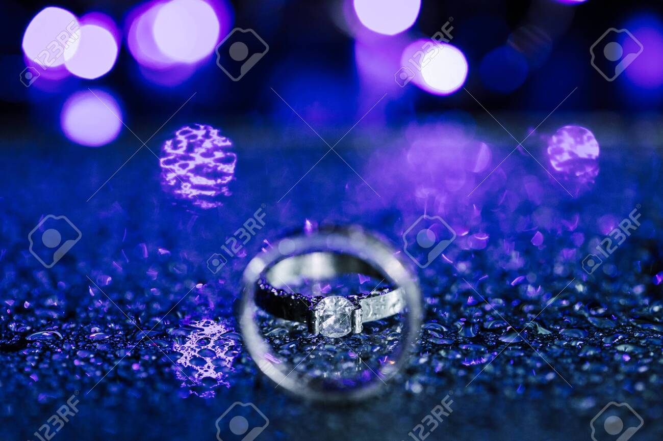 Close up diamond ring wedding ring inside circle. Creative wedding invitation card concept. Sparkling purple background with copy space. - 128126346