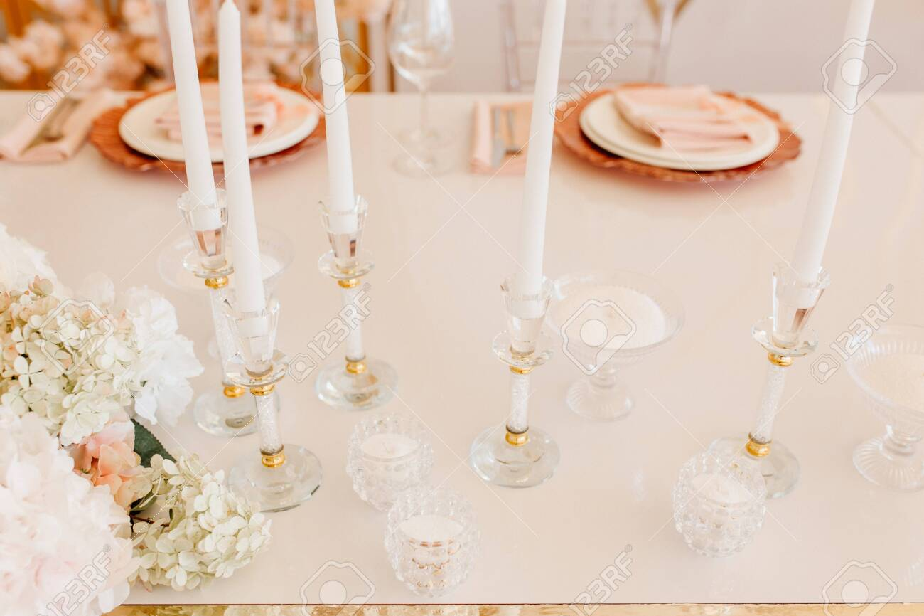 Candles Atanding in Crystal Decorative Candlsticks and Flower Bouquet on Dining Table Horizontal Photography. Napkin on Plates for Delicious Meal and Wine Glasses on Blurred Background - 138172179