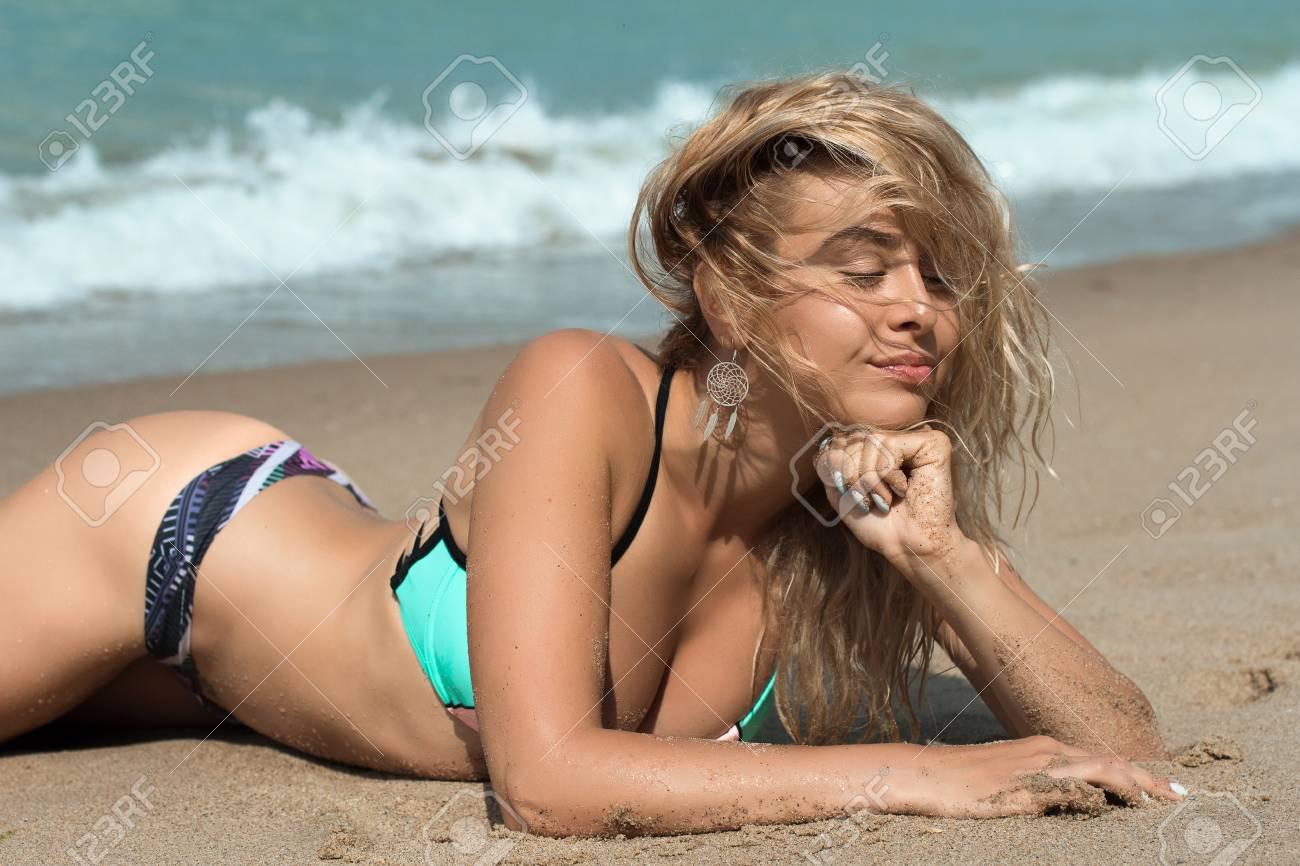 ede2cbd32f Archivio Fotografico - Ragazza sexy e intelligente è sdraiata sulla  spiaggia in un bellissimo costume da bagno