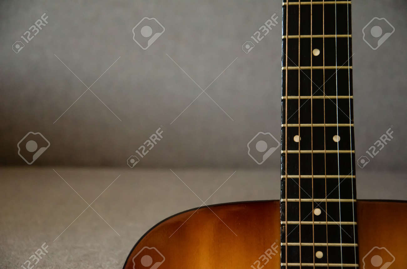 Close-up guitar fretboard with strings isolated on a blurred gray background with copy space. Music concept. Gray fabric surface. The creative process. - 158840316