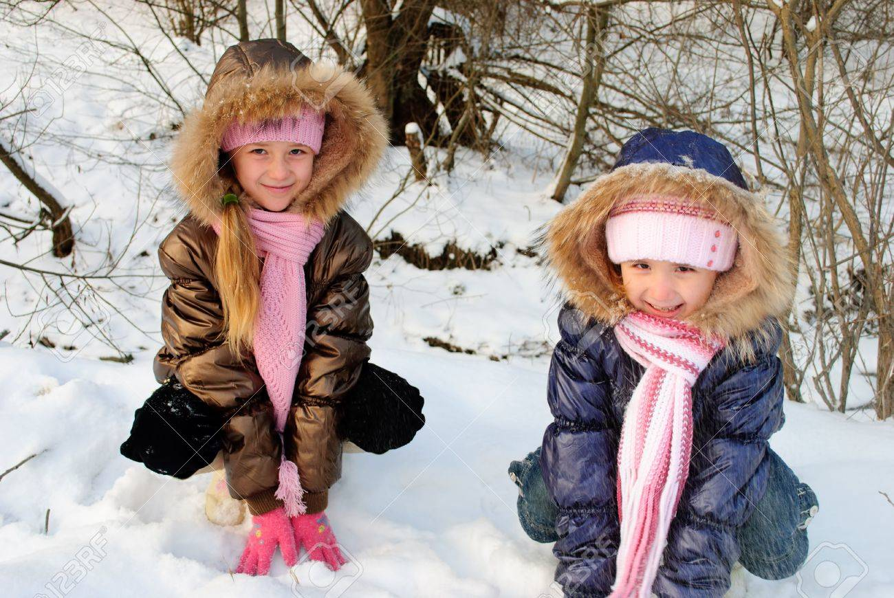 Two little sisters playing with snow outdoors Stock Photo - 7878298