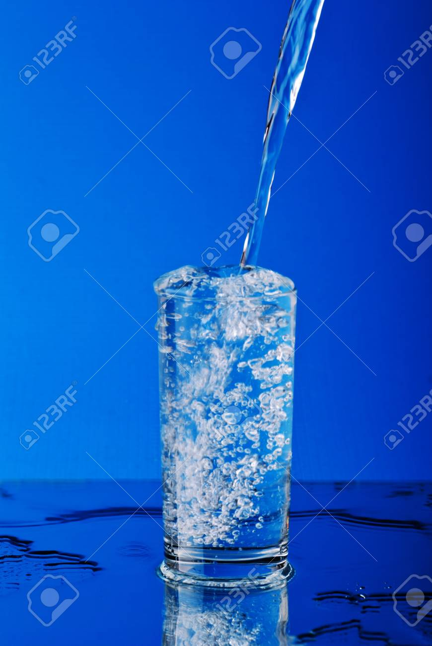 Puring water into the glass on blue Stock Photo - 8870156