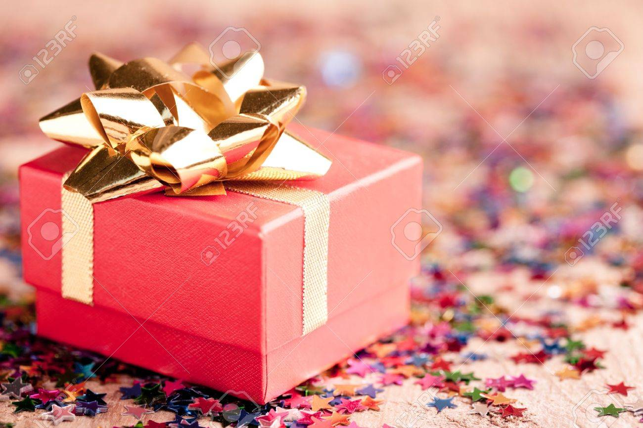 Small red gift box closeup with gold bow special for jewelery - 10432509