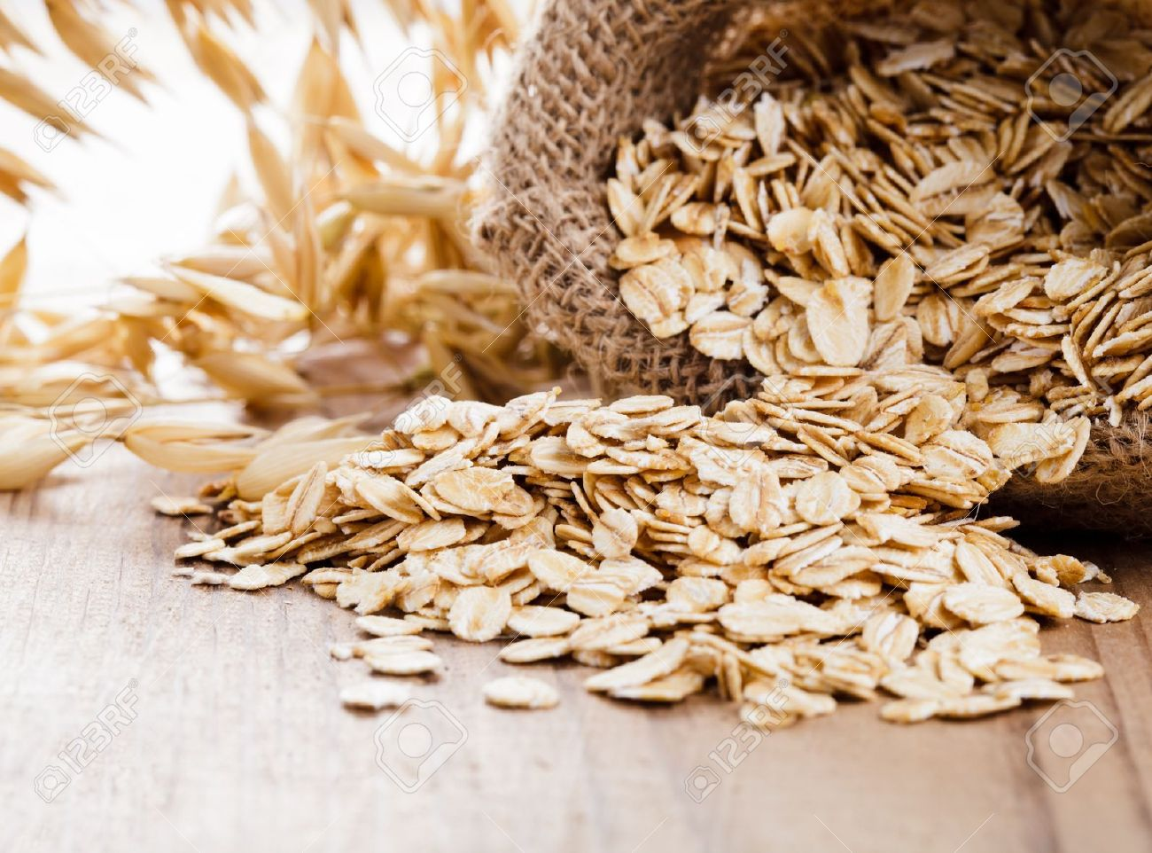 Oat flakes spilling from the burlap bag on wooden table Stock Photo - 10786482