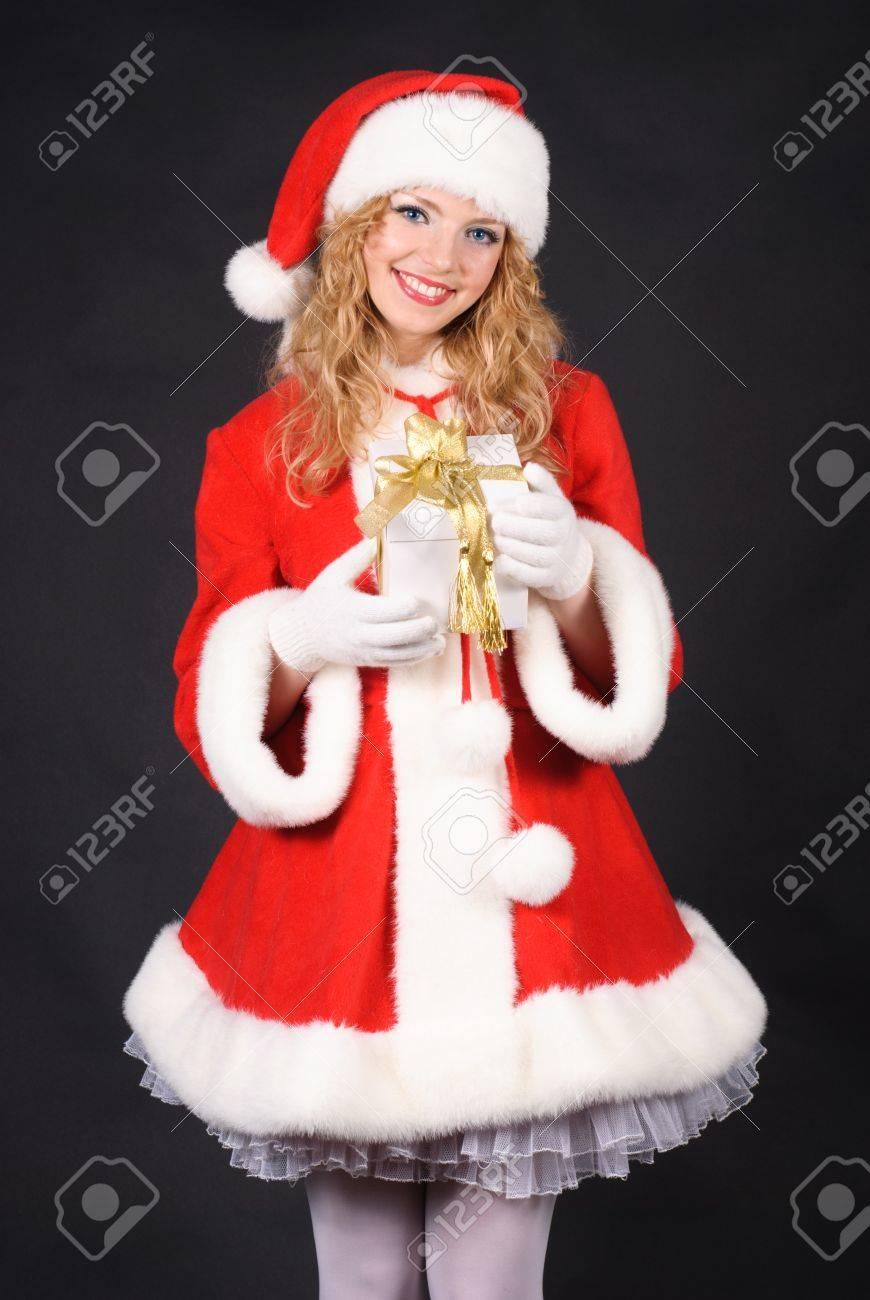 Christmas santa girl with gift isolated on black. Copy text. Christmas greetings card Stock Photo - 10942617
