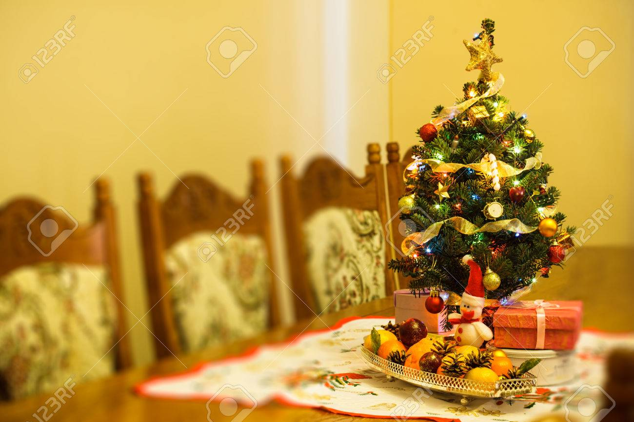 small christmas tree with decorations gifts and citrus on the table stock photo 22360294