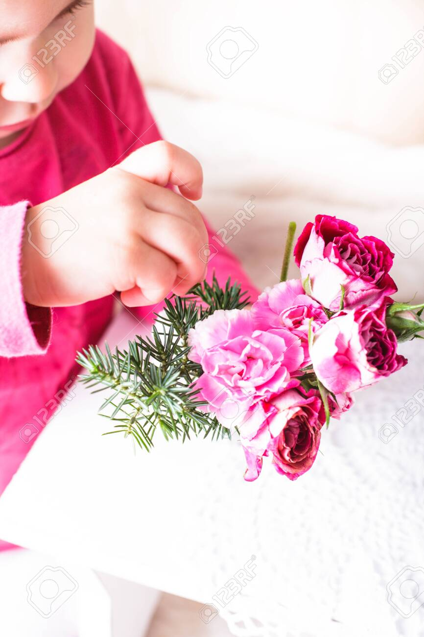 Little girl is smelling the roses. Close up face Stock Photo - 27161289