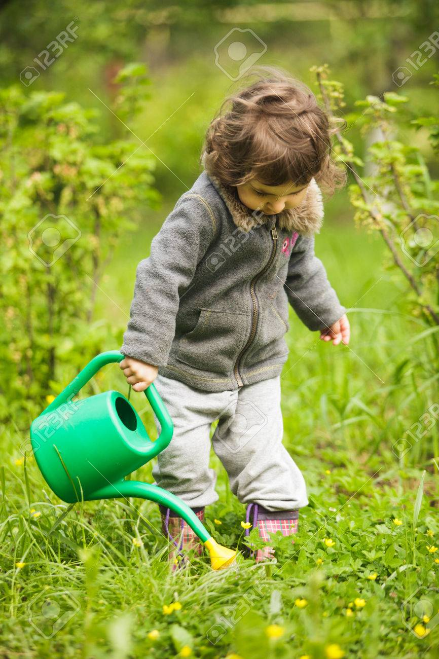 Little kid with watering can in the garden Stock Photo - 28753678
