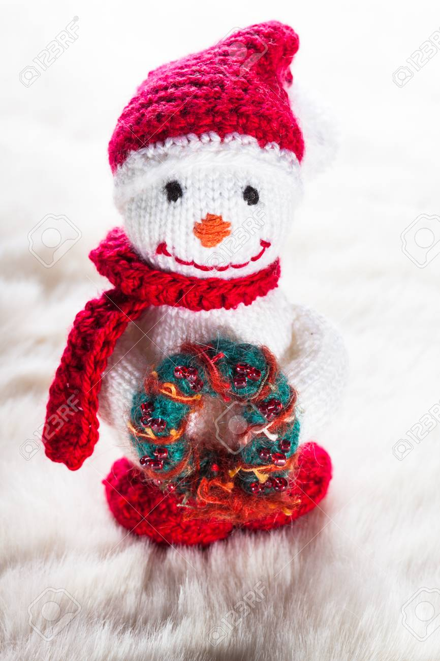 Knitted Snowman With Christmas Wreath On White Snow Stock Photo