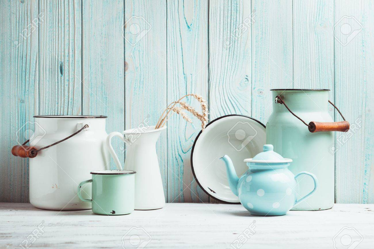 Enamelware on the kitchen table over blue wooden wall - 37860150