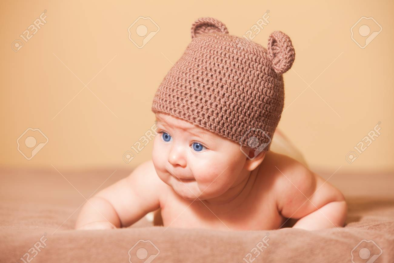 6885250afd05 Adorable baby in bear hat lying on the bed Stock Photo - 47946764
