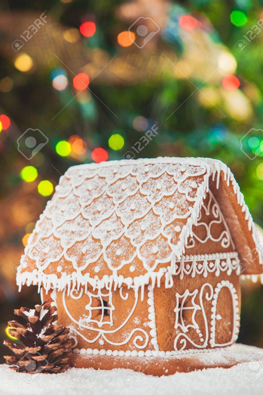 gingerbread house over defocused lights of Chrismtas decorated fir tree - 49835599