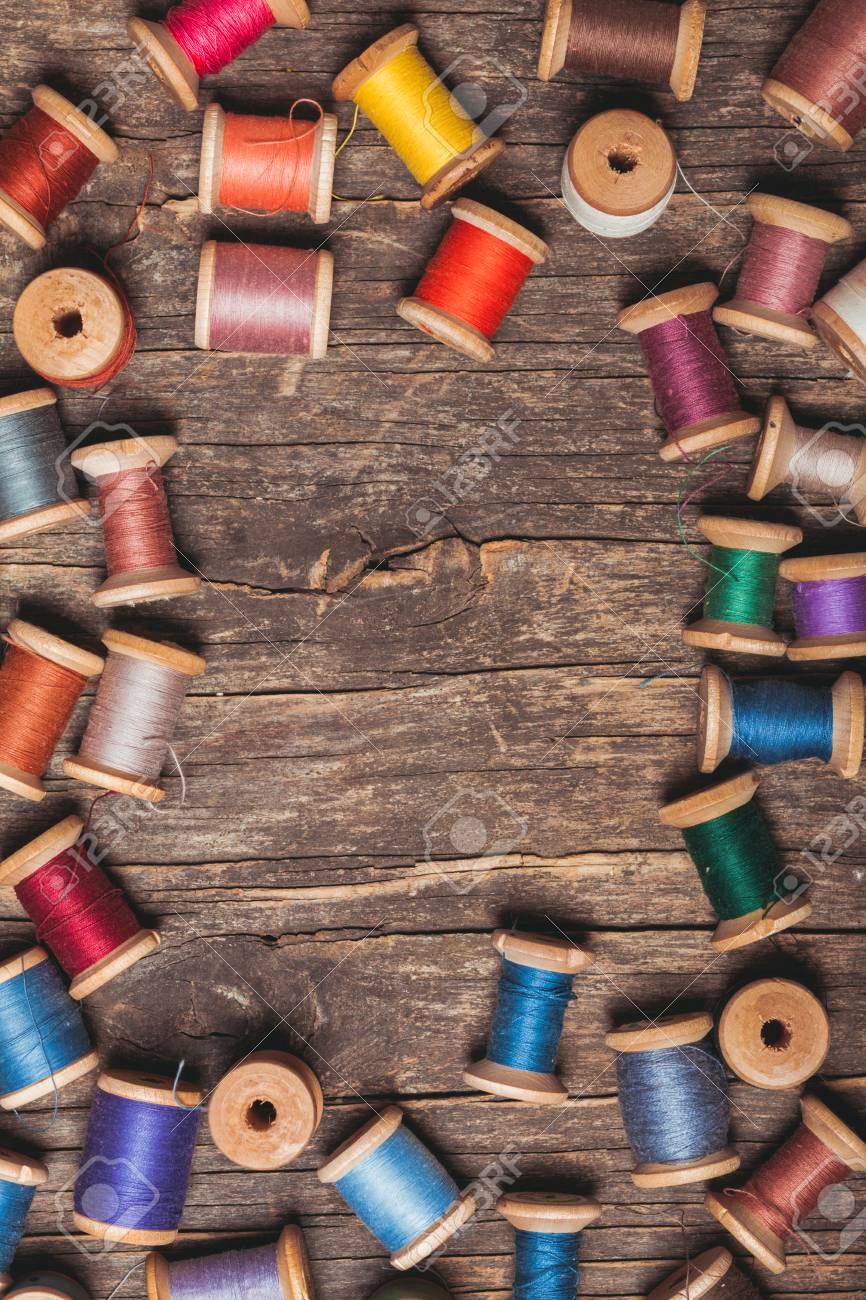 Retro Wooden Sewing Spools With Colourful Threads Over Vintage