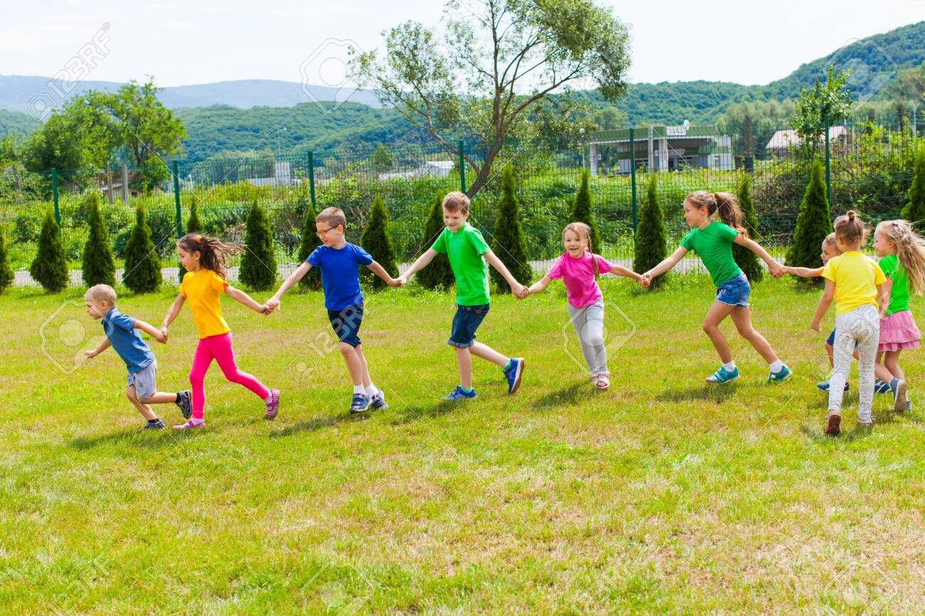 Kids run holding hands outdoor. Girls and boys have fun - 130463116