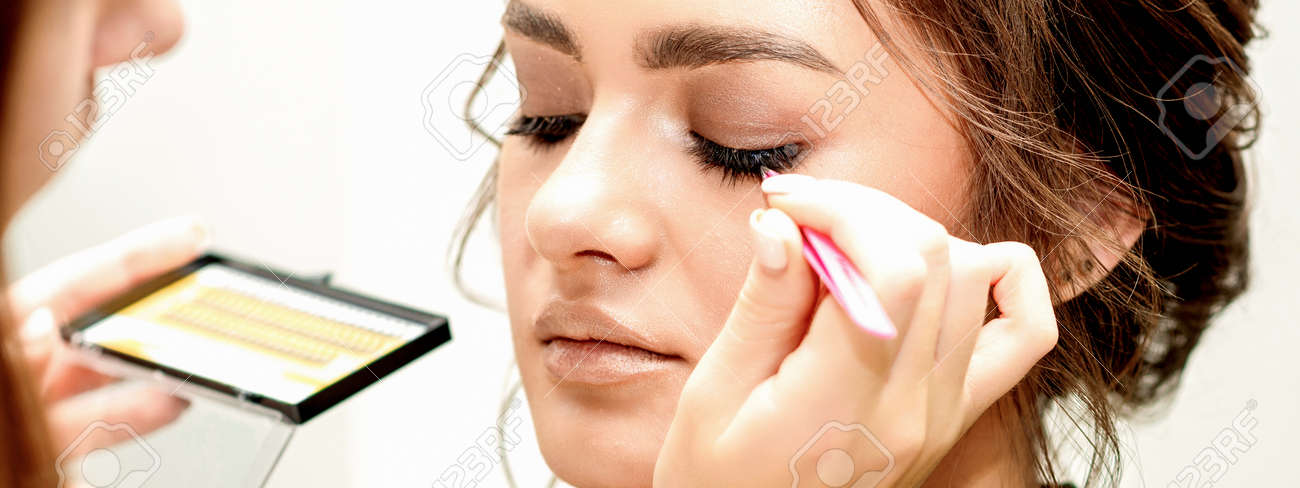 Eyelash extension procedures. Beautiful young caucasian woman receiving eyelash extension by master in a beauty salon - 169731276