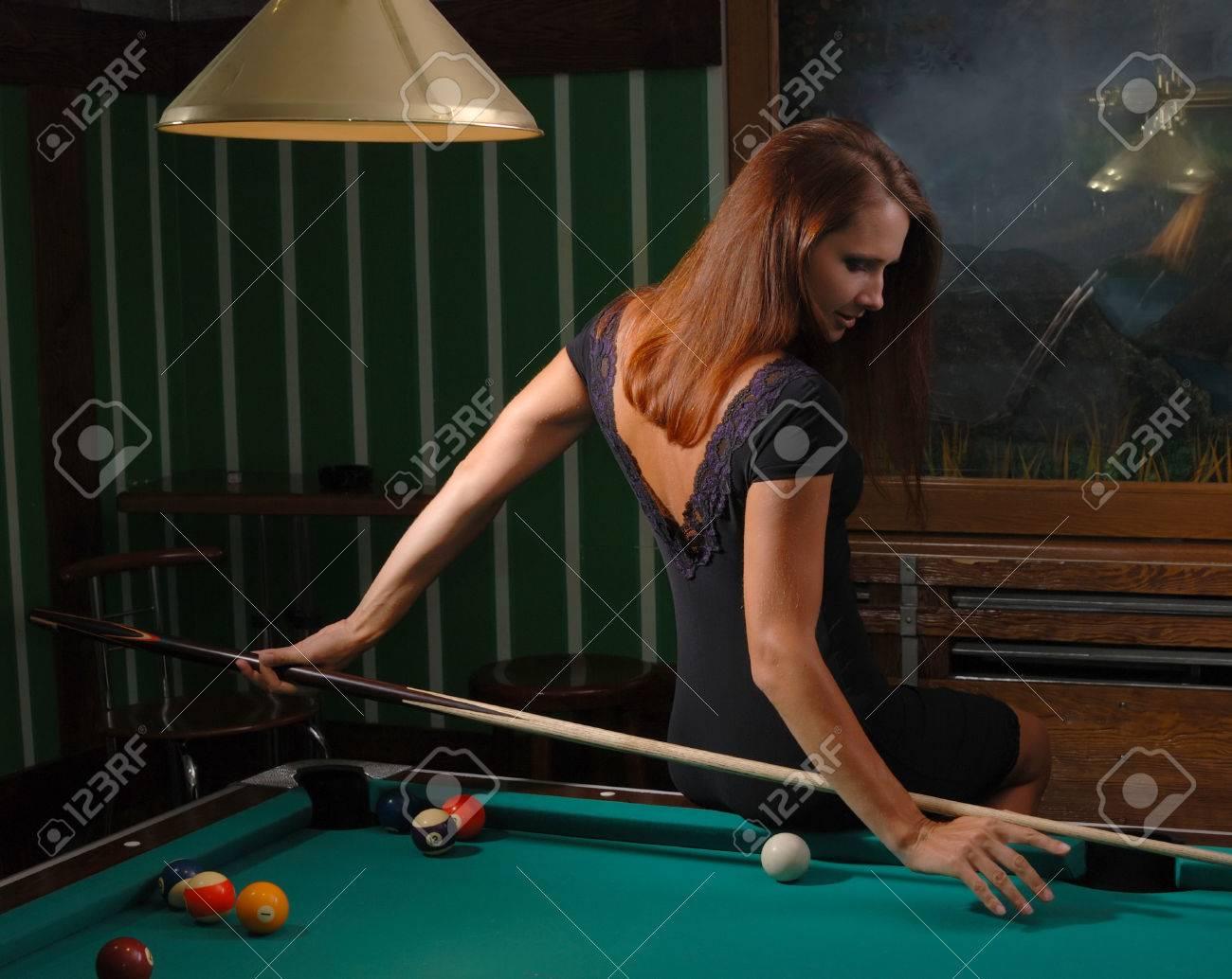 Mujer de vestido rojo jugando billar