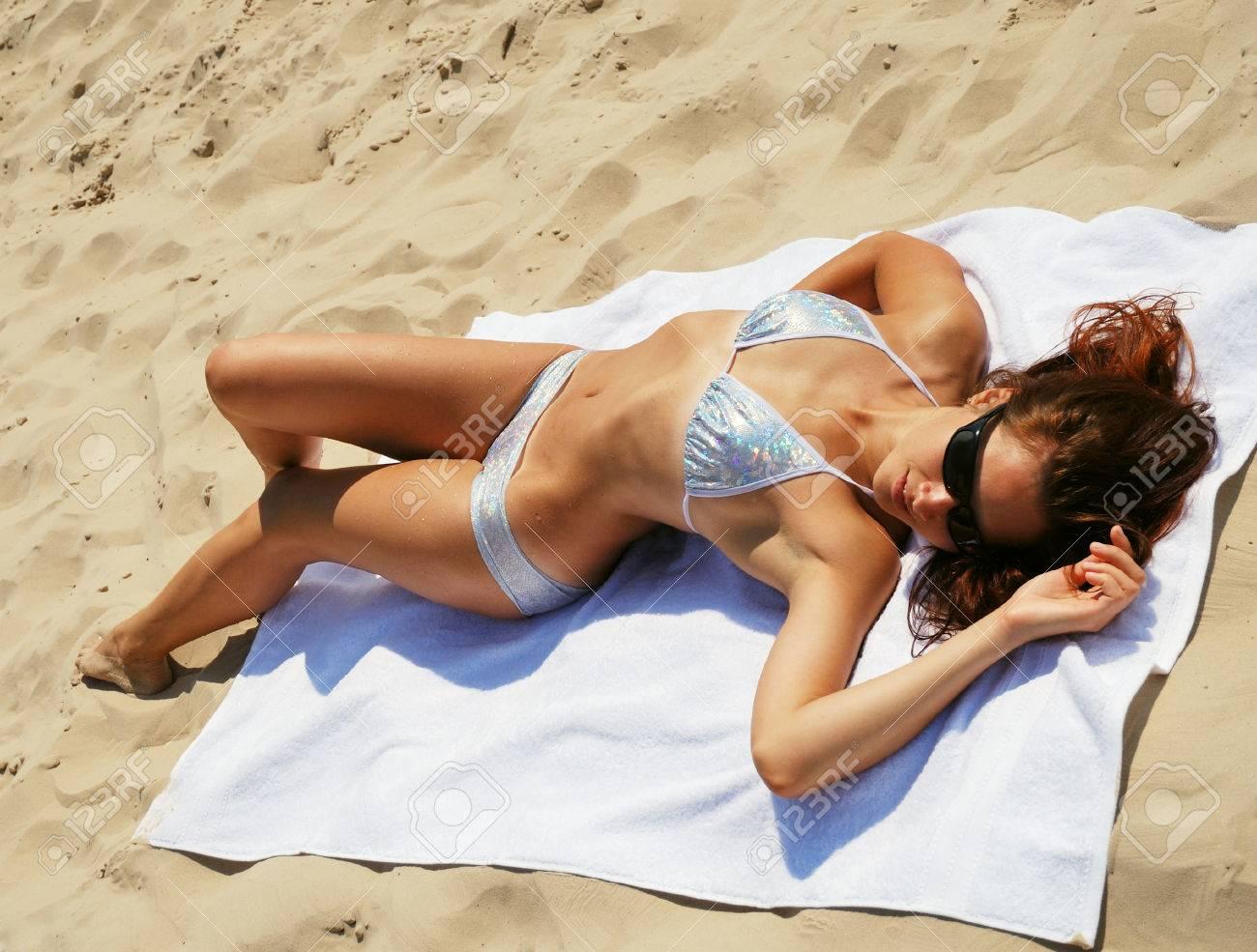 c015afb8fc49 La mujer joven está tumbado en la toalla blanca Ella lleva bikini y gafas  de sol que brilla Ella está adquiriendo un bronceado en la playa de arena
