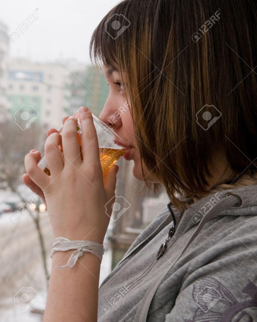 Slikovnica 4187230-La-ragazza-dei-costi-su-un-balcone-e-beve-il-t-caldo-Dietro-una-finestra-invernale-strada--Archivio-Fotografico