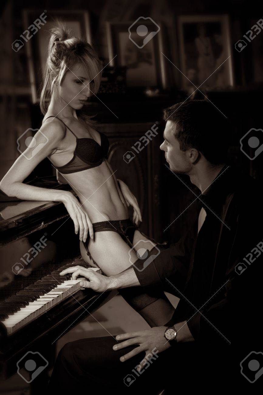 The musician plays the old piano, nearby the seductive woman Stock Photo - 8569811