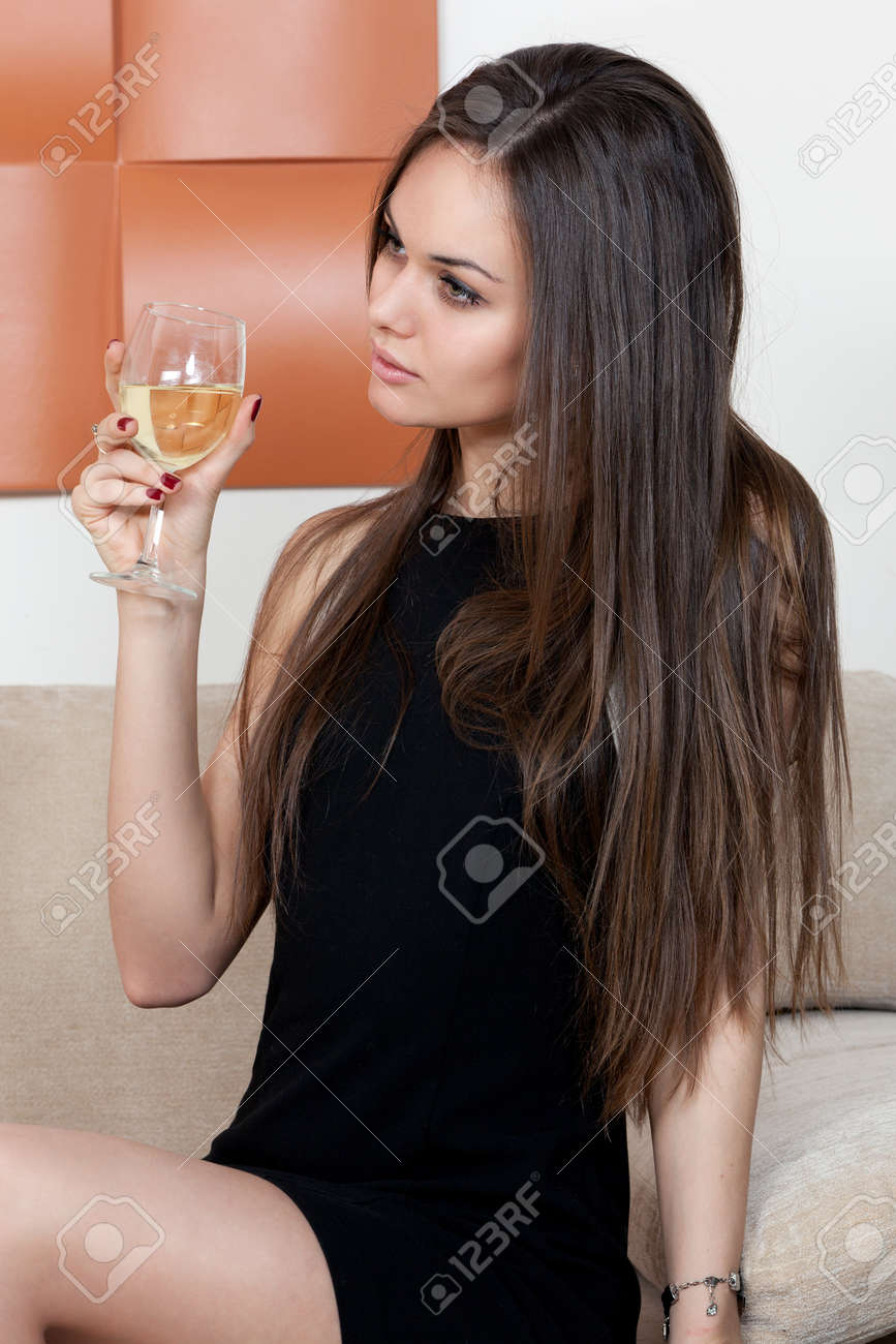 Elegant woman with a glass of wine sitting on the sofa Stock Photo - 19387644