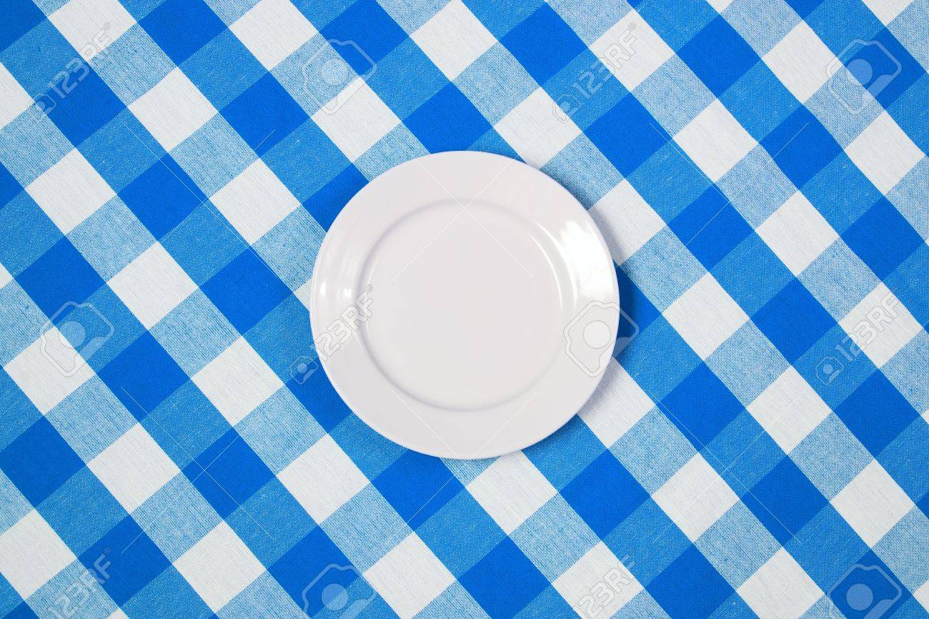 Stock Photo   White Round Plate On Blue Checked Tablecloth