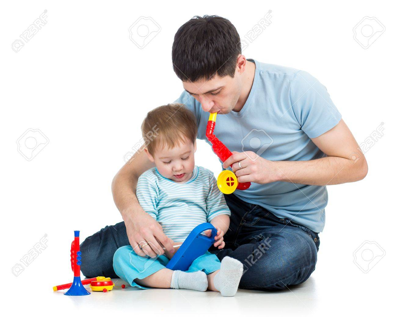 Father and baby boy having fun with musical toys   Isolated on white background Stock Photo - 17499573